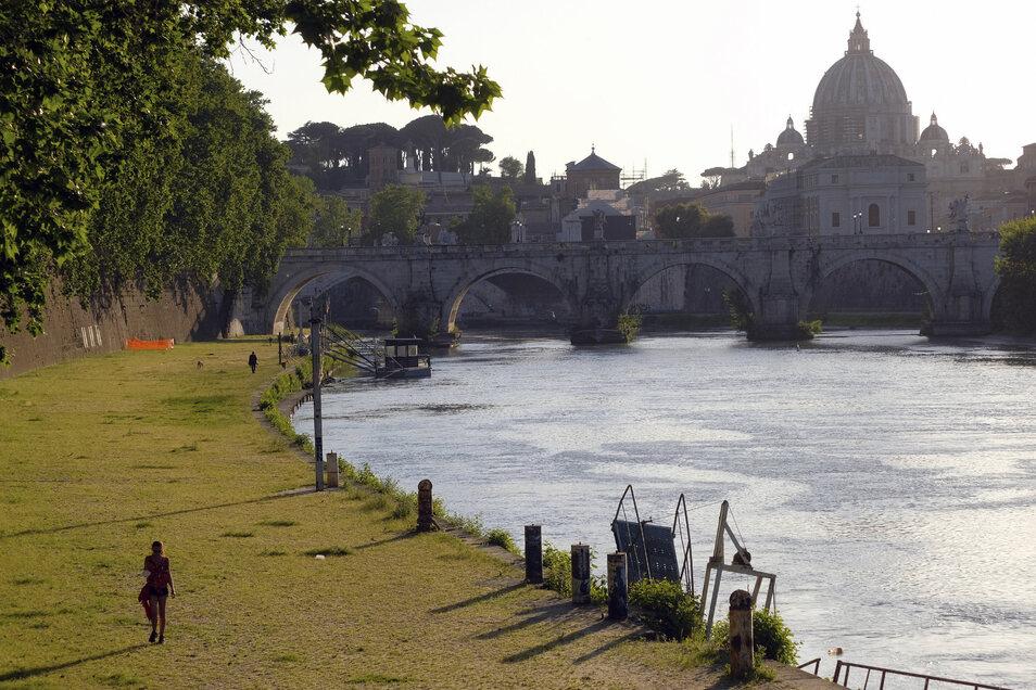 Eine Frau geht in Rom am Ufer des Tibers entlang. Italien lässt erste Lockerungen zu.