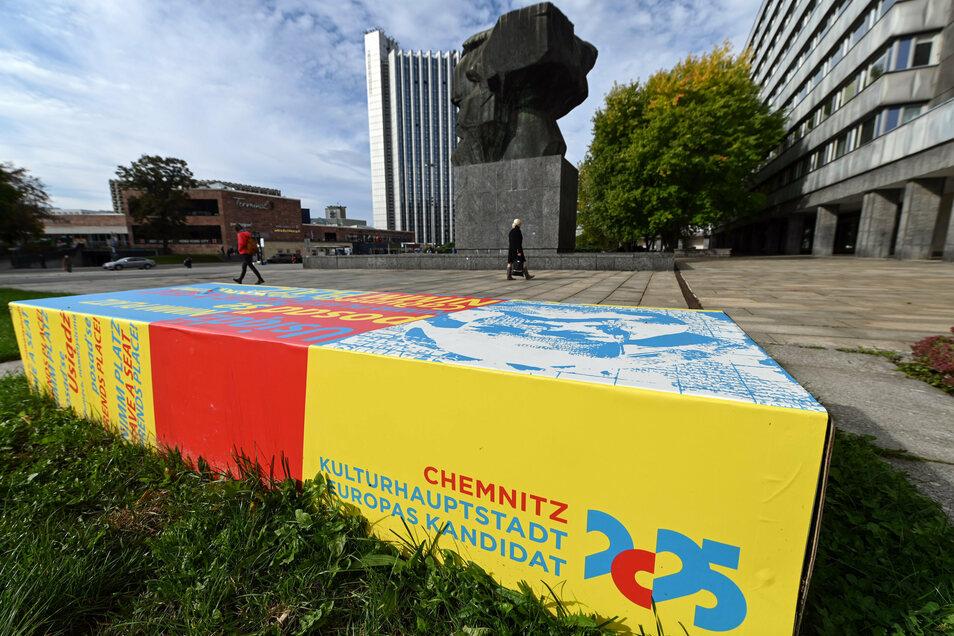 """""""Chemnitz, Kulturhauptstadt Europas Kandidat 2025"""" steht auf einer Bank am """"Nischel"""" genannten Karl-Marx-Monument."""