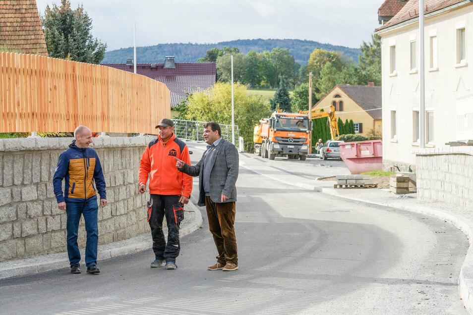 SLB-Geschäftsführer Silvio Buchhorn (v. r.), Polier René Häßler und Bürgermeister Olaf Reichert sind guter Dinge: Die Ortsdurchfahrt in Jenkwitz verleiht dem Dorf ein neues Gesicht. Der Weg dahin war kompliziert.