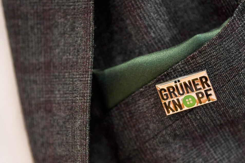 Faire Kleidung: Der Anstecker zeigt das Symbol für das staatliche Textilsiegel Grüner Knopf.