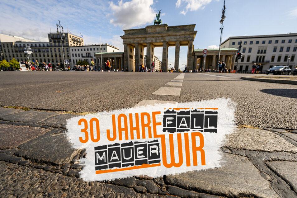 An der Stelle, wo zu DDR-Zeiten die Berliner Mauer stand, sind vor dem Brandenburger Tor Pflastersteine zu sehen, die an die Mauerzeiten erinnern. Noch immer gibt es viele Unterschiede zwischen Ost und West bei Einkommen, Vermögen und mehr.