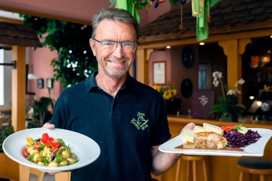 """""""Haseneck""""-Chef Frank Haase hält in der rechten Hand eine vegetarische Gnocchipfanne mit Senfsoße, in der linken Kaninchenroulade mit Senfsoße."""