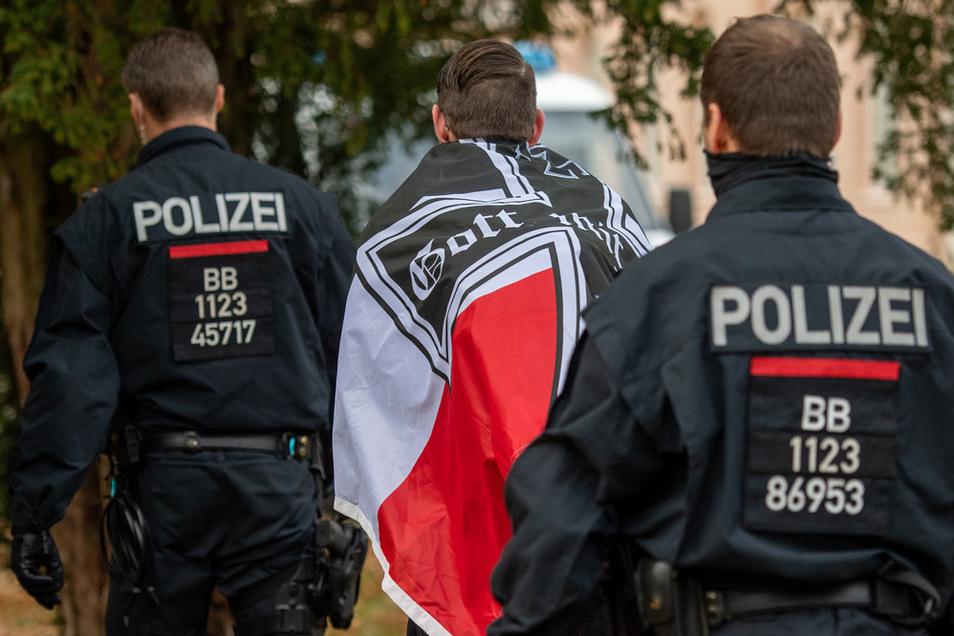 Ein Demonstrant mit einer schwarz-weiß-roten Flagge mit einem Eisernen Kreuz darauf wird von zwei Polizisten abgeführt während einer Demonstration von sogenannten Reichsbürgern.