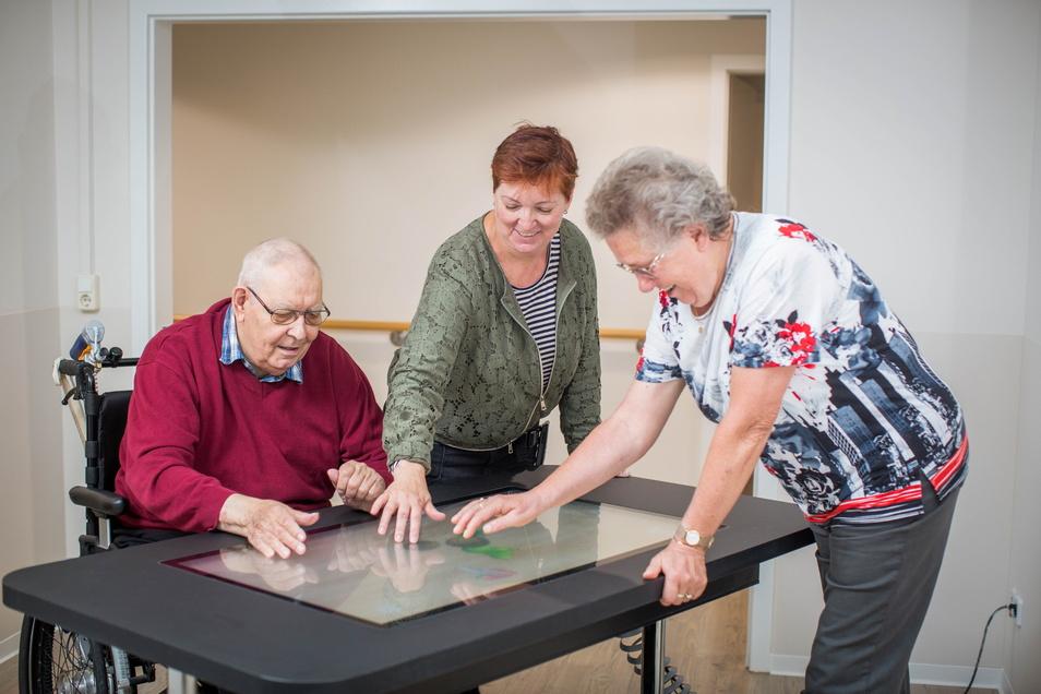 Hartmut Ehrhardt und Annemarie Schulze (r.) lassen sich im ASB-Seniorenheim in Gorbitz von Kerstin Leuteritz den virtuellen Spieletisch erklären.