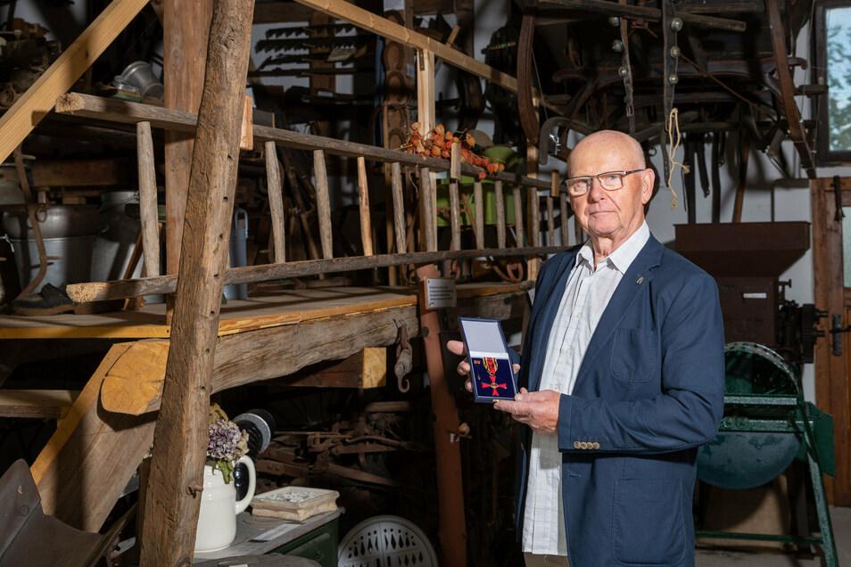 Kurt Weißhaupt steht mit seinem Bundesverdienstorden in der Museumsscheune in Rathewalde, die der selbst mit aufgebaut hat.