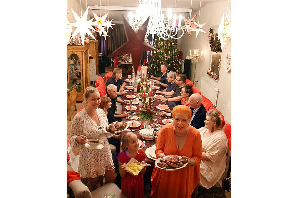 Martina Sawatzke steht mit ihrer achtjährigen Enkeltochter Alisia und ihrer Tochter Eva (r-l) mit dem Festessen im geschmückten Weihnachtszimmer.