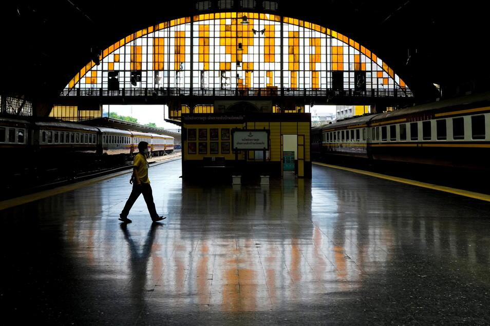 Ein Mann geht über den menschenleeren Bahnsteig der 104 Jahre alten Hua Lamphong Railway Station in Bangkok.