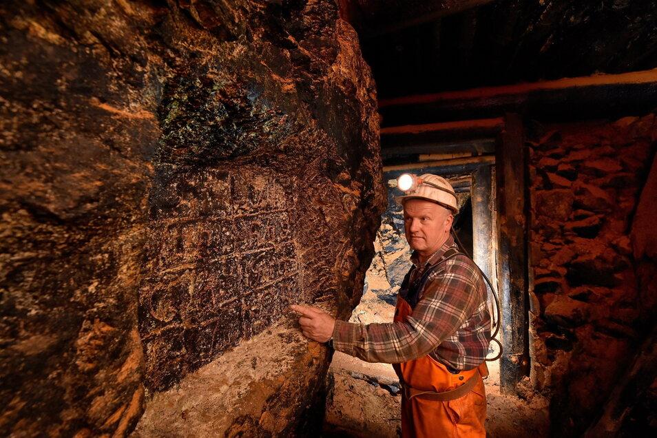 Thomas Witzke, Mitarbeiter der Bergsicherung Freital, steht hier an der in den Fels gehauenen Tafel, die an dem Fund eines Erzgangs 1798 erinnert.