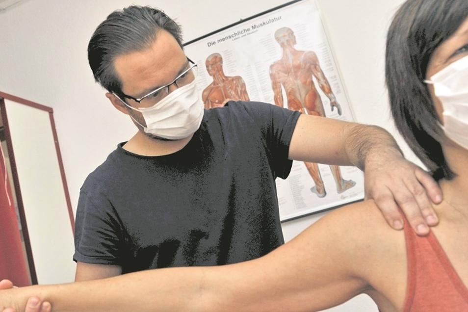 Physiotherapeut Stefan Seidel behandelt ein Schultergelenk nach einem Belastungsschmerz. Vor zehn Jahren hat der Weißwasseraner seine eigene Praxis gegründet – und darf sie bei Einhaltung der bekannten Hygieneauflagen auch in Corona-Zeiten öffnen.