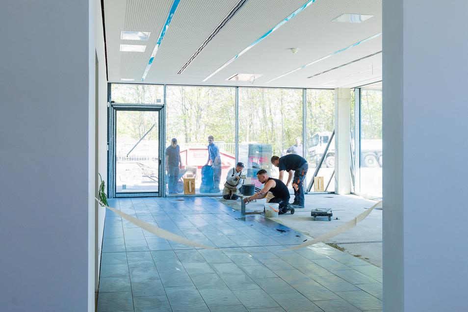 Im künftigen Raum für die Pressekonferenzen und Medienarbeit werden derzeit die Fliesen gelegt. Insgesamt sind in dem dreigeschossigen Funktionsgebäude 1.600 Quadratmeter Fußböden und Streppenstufen zu fliesen.