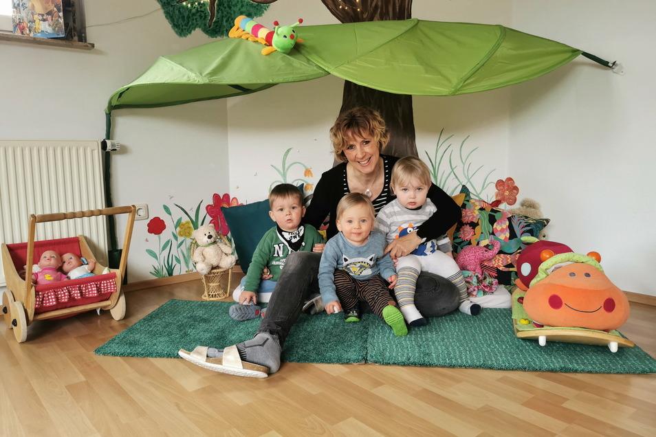 """Ines Hempel aus Meißen mit den drei Jungs ihrer fünf Schützlinge im Spielezimmer des """"Raupennestes"""" in Klipphausen."""