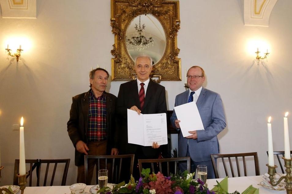 Sachsens Ministerpräsident Stanislaw Tillich übergibt Ottendorfs Bürgermeister Michael Langwald (r.) und Steffen Frenzel (l.) von der Interessengemeinschaft die Fördermittel vom Bund und vom Freistaat.