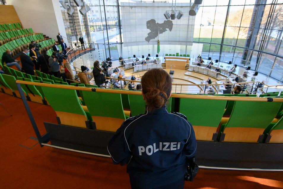 Eine Polizistin verfolgt die Sondersitzung des Innenausschusses und des Verfassungsausschusses im Sächsischen Landtag