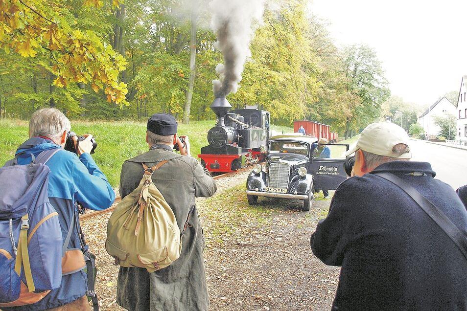 Eine historische Dampflok samt Waggons von der Waldeisenbahn Muskau neben einem Oldtimer: Das sind die Motive, die Teilnehmer von Fotozug-Reisen erwarten und beglücken.