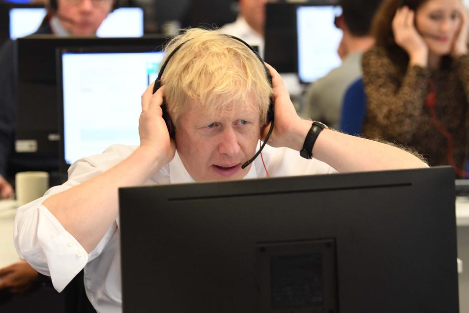 Boris Johnson, Premierminister von Großbritannien, sitzt mit anderen Kabinettsmitgliedern mit Headset vor einem Bildschirm an einem Tisch im Call Center des Hauptquartiers der Konservativen während des Wahlkampfs.
