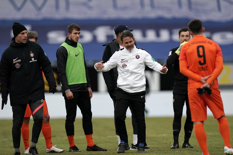Aues Trainer Dirk Schuster spricht nach der 1:4-Niederlage mit seinen Spielern.
