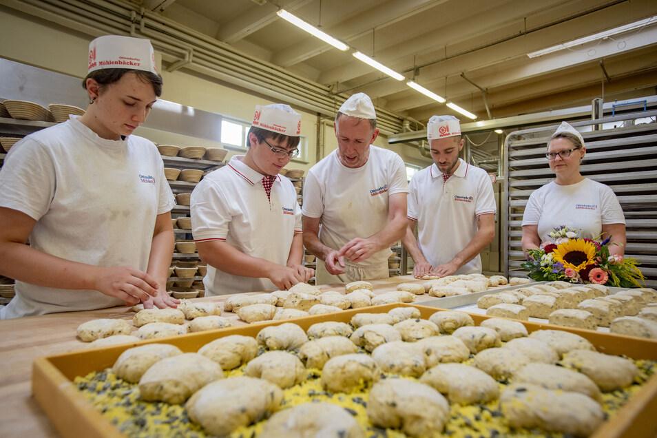 Bäckermeister Frank Wunderlich (Mitte) zeigte gestern den neuen und ehemaligen Azubis, wie man Kürbiskernbrötchen macht. Interessiert schauen die frischgebackene Bäckergesellin Sophie Bartzsch (l.) sowie die Azubis Marcel Zschieschack (2.v.l.) und Jo-Bob