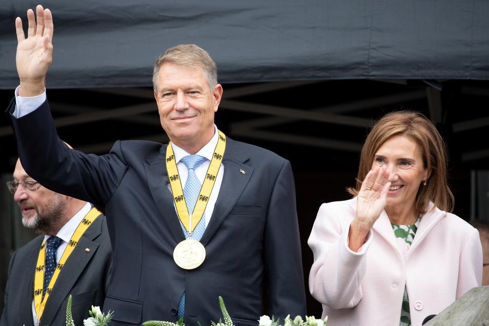Iohannis und seine Frau Carmen stehen auf den Stufen des Rathauses und winken den Menschen zu.