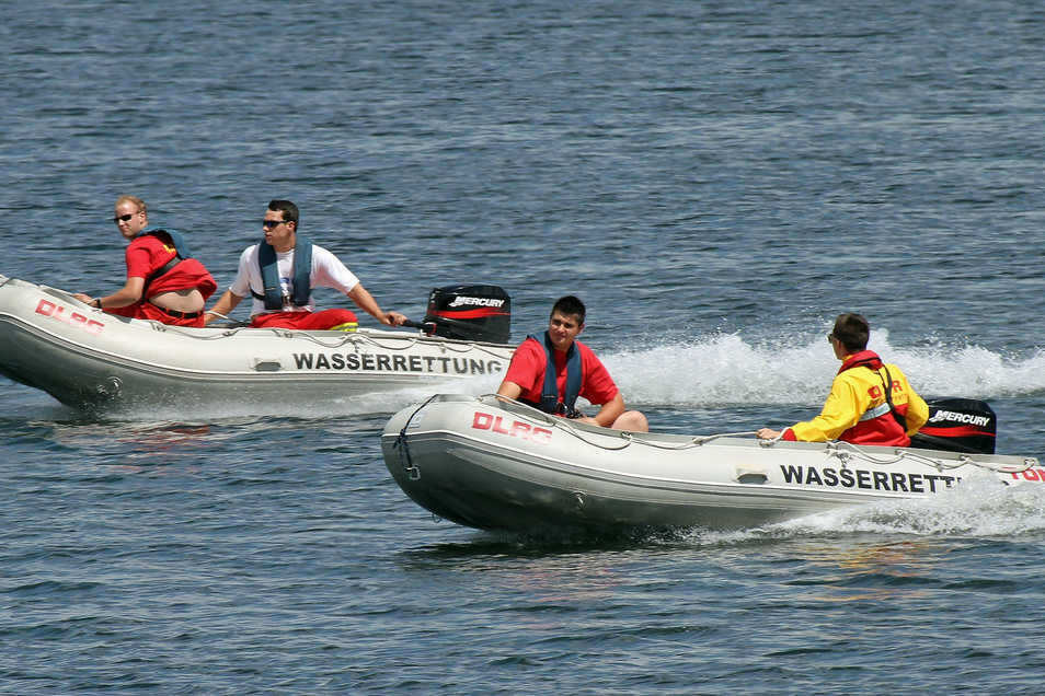 Rettungsschwimmer sind mit ihren Booten auf dem See unterwegs.
