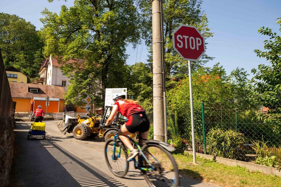 Ohne das Stoppschild zu beachten, rasen die Radfahrer die Straße entlang. Vorfahrt hat eigentlich das Baufahrzeug.