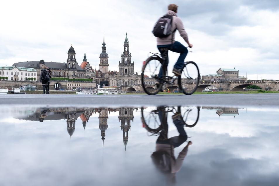 Immer wieder Schauer in Sachsen: Ein Radfahrer fährt am Ufer der Elbe vor der Kulisse der Dresdner Altstadt entlang und spiegelt sich in einer Pfütze.