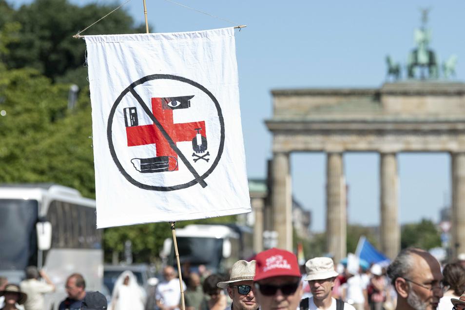 Eine Fahne, auf der Symbole aus einem Roten Kreuz ein Hakenkreuz formen, zeigt dieser Teilnehmer.