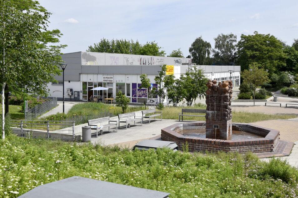 """Der Flachbau, in dem sich früher der """"Grüne Heinrich"""" befand, wird demnächst abgerissen. Der Märchenbrunnen im Vordergrund steht dagegen seit 2018 unter Denkmalschutz."""