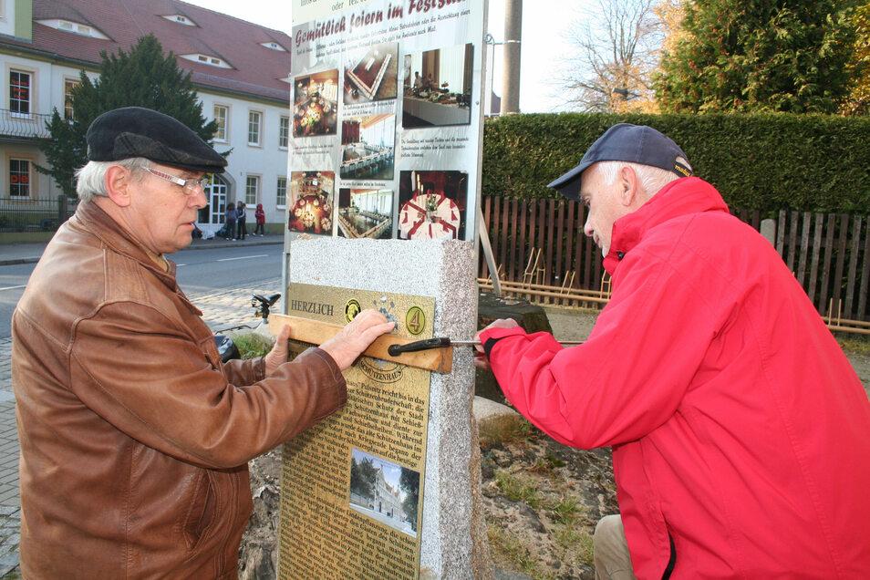 Die Heimatvereinsmitglieder Hartmut Hermann (l.) und Manfred Voit befestigen eine Informationstafel auf einem der historischen Wegesteine in Pulsnitz.