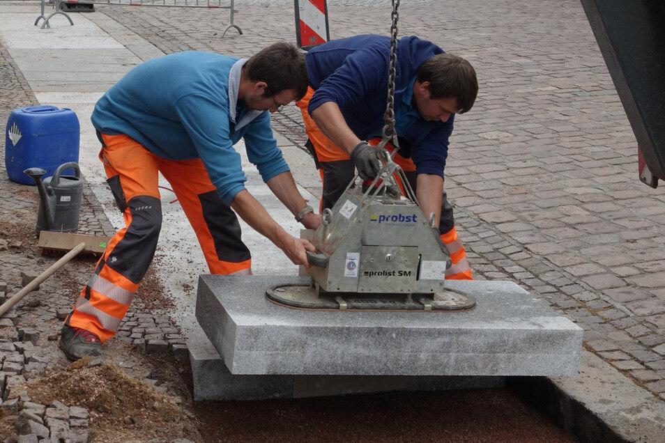 Mitarbeiter des Bauhofs verlegen neue Gehwegplatten.