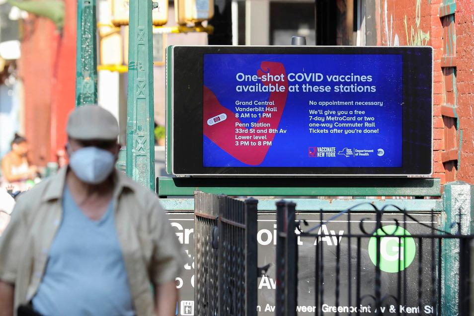 New York: Ein Fußgänger geht an einem Werbeplakat für Corona-Schutzimpfungen in Bahnhöfen vorbei.