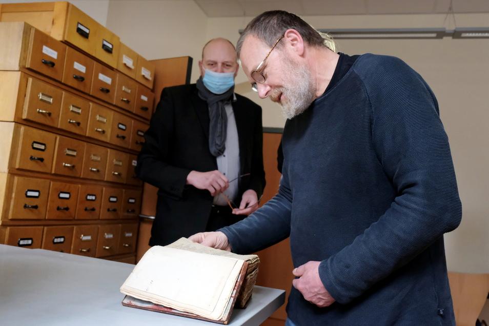 """Tom Lauerwald (rechts) studiert zufrieden die Stadtchronik Meißens. Oberbürgermeister Olaf Raschke (parteilos): """"Es ist ein kleines Wunder, dass es die Chronik noch gibt."""""""