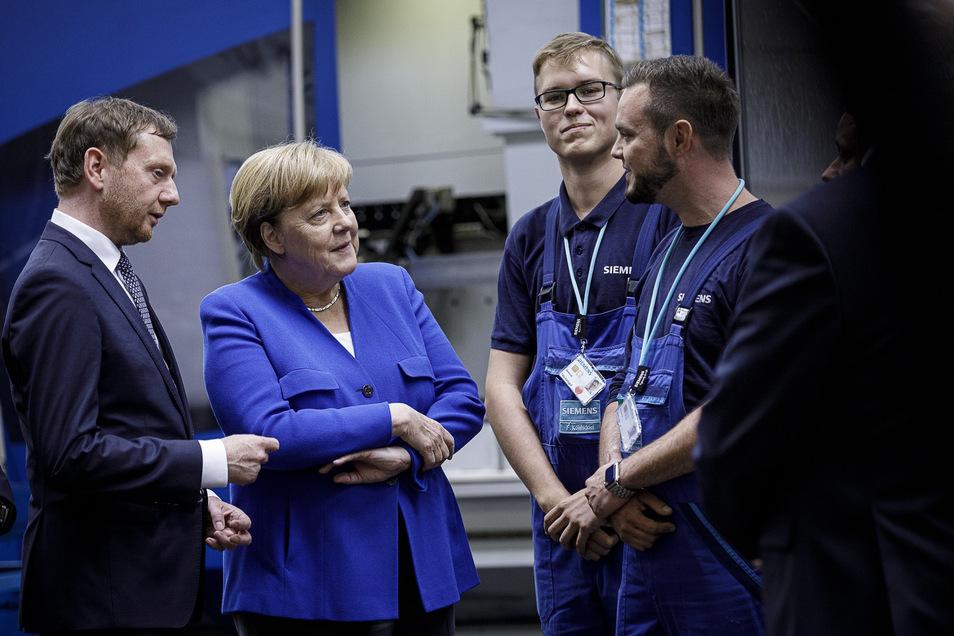 Siemens-Mitarbeiter Martin Nitsche (re.) und Felix Kohlsdorf (2. v. re.) trafen gestern mit Bundeskanzlerin Angela Merkel und Sachsens Premier Michael Kretschmer zusammen.
