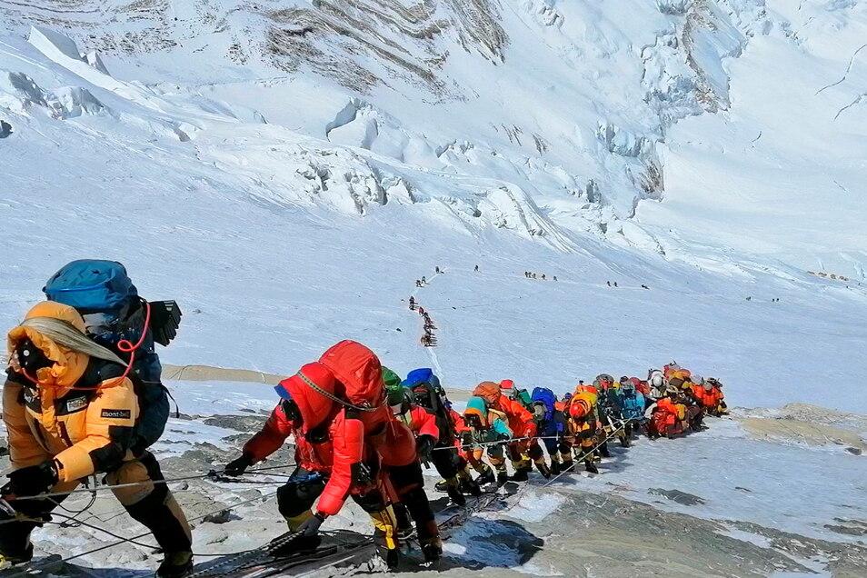 In einer langer Schlange klettern Bergsteiger auf einem Pfad knapp unterhalb von Lager vier. Wird es nach einem Jahr Lockdown 2021 am Mount Everest wieder so aussehen?