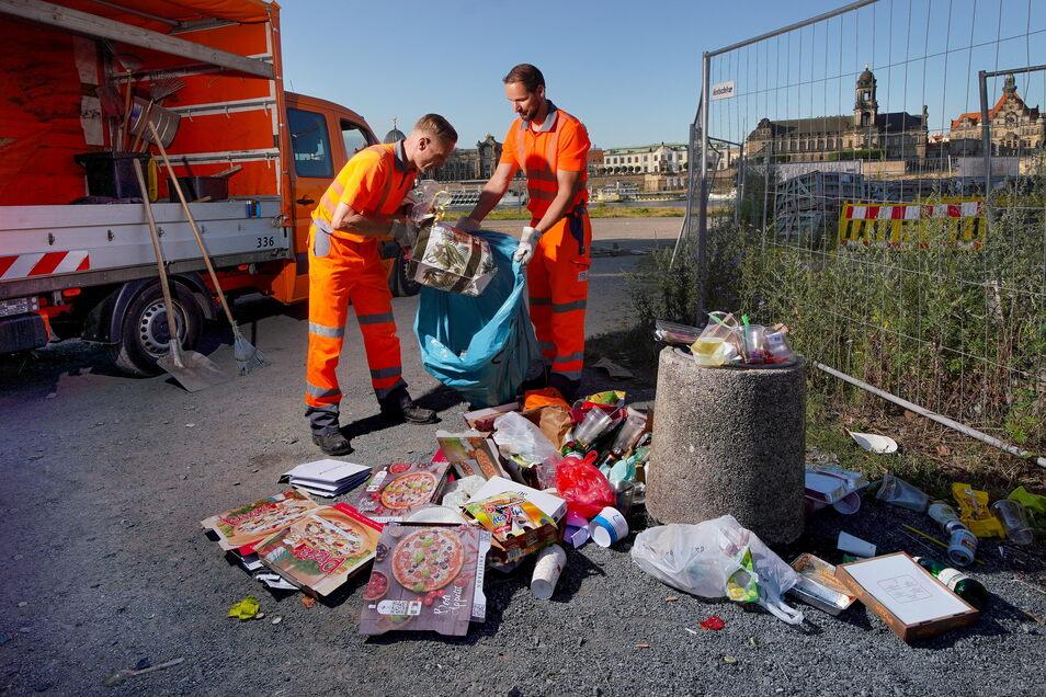 Mitarbeiter der Stadtreinigung Dresden tragen Müll vom Elberadweg weg.