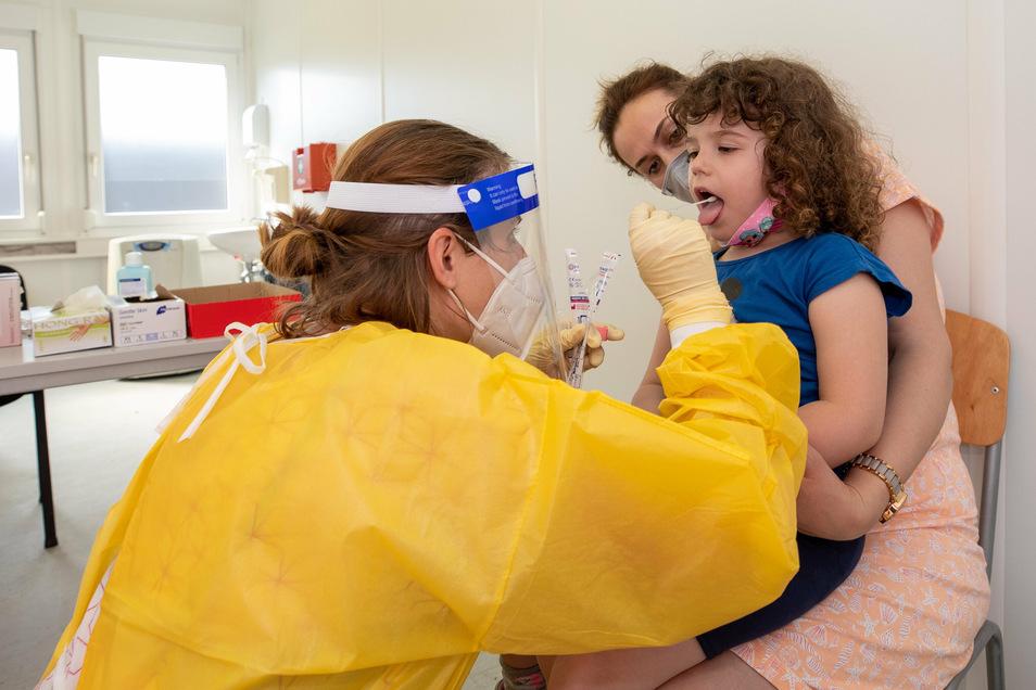 Corona-Test beim Kind: Ein dreijähriges Mädchen wird von ihrer Mutter gehalten, damit Ärztin Annelie Ölschläger mit einem Teststäbchen einen Abstrich machen kann.