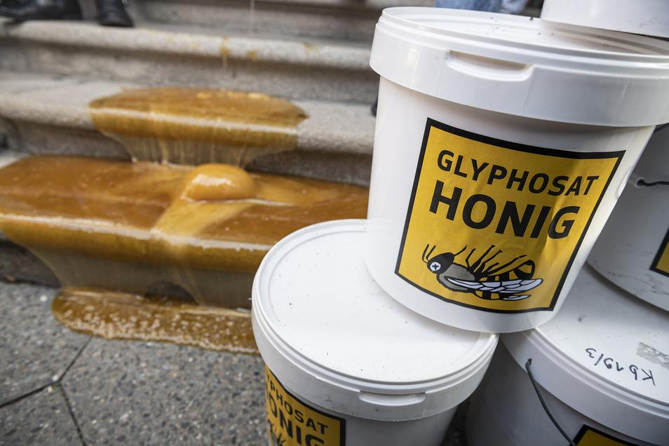 Eimer mit Glyphosat-belasteten Honig der Brandenburger Imkerfamilie Seusing stehen vor dem Landwirtschaftsministerium in Berlin.