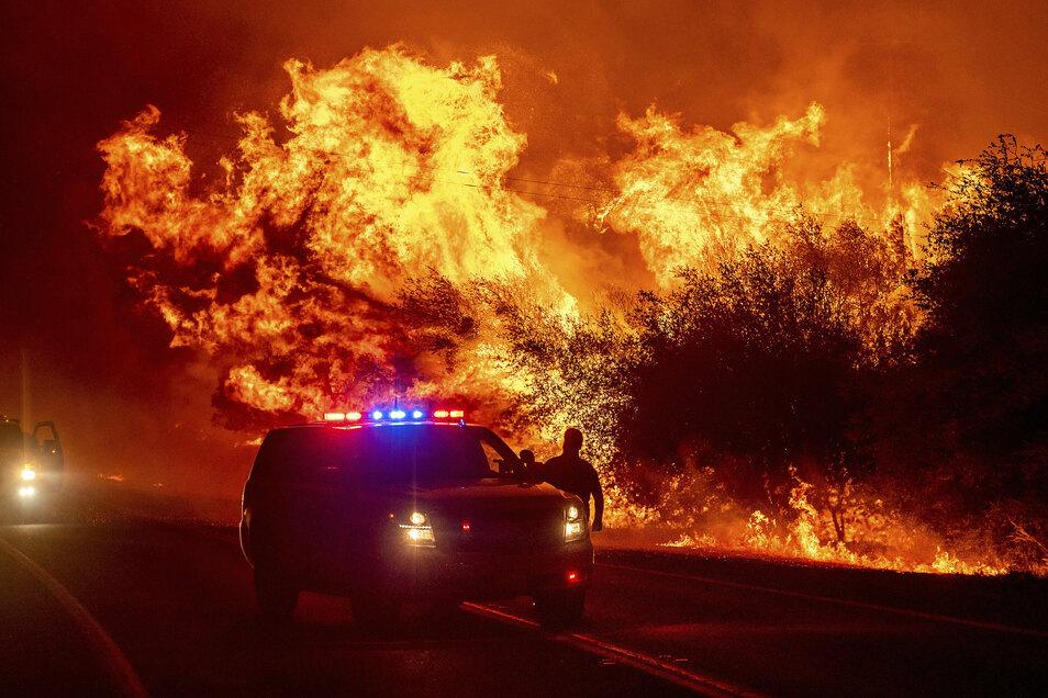 USA, Oroville: Hinter einem Auto mit Blaulicht steigen Flammen auf der Highway 162 auf.