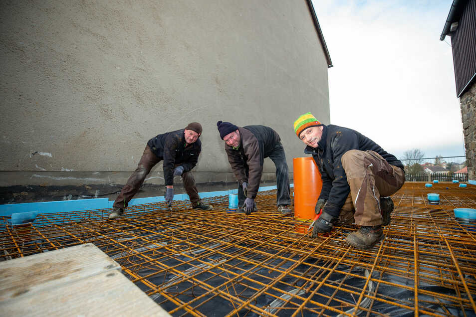 Steffen Steudtner (v.l.), Matthias Badeja und Thomas Vogt von der Firma Bau-Martin aus Wehrsdorf bei Sohland sind dabei, die Bodenplatte zu bewehren. Mit rund 300 Verbindungsdrähten wird diese festgezurrt.