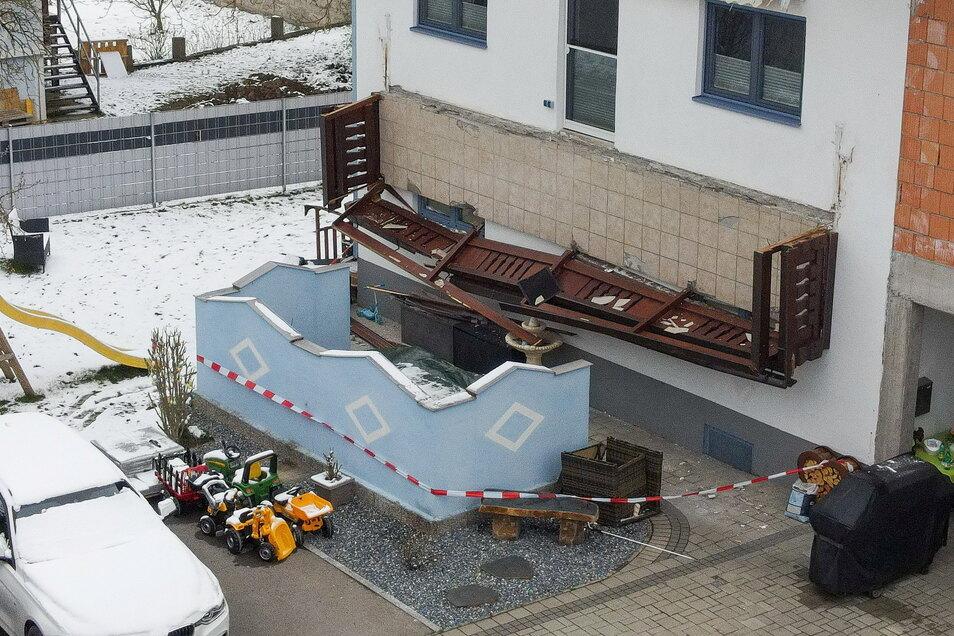 Der abgestürzte Balkon hängt senkrecht an einer Hauswand.