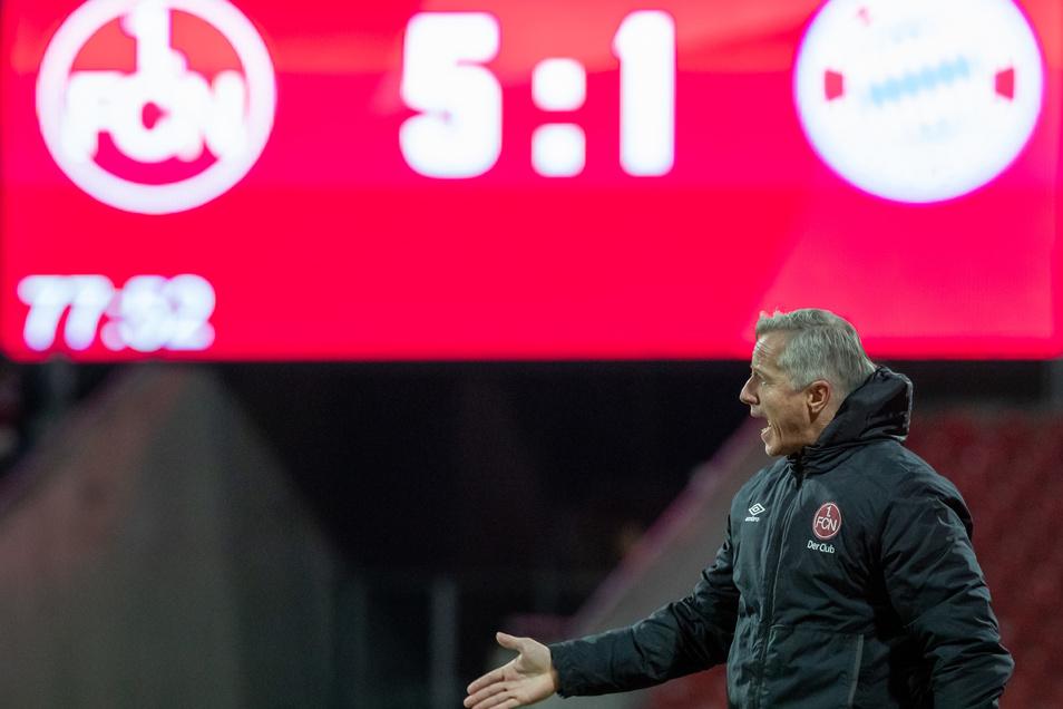 Der Nürnberger Trainer Jens Keller gestikuliert am Spielfeldrand, während auf der Anzeigetafel das zwischenzeitliche 5:1 gegen die Bayern zu sehen ist.