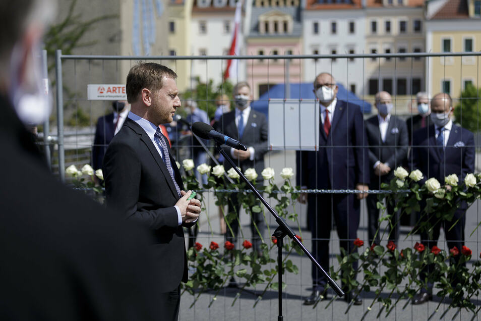 Sachsens Regierungschef Michael Kretschmer beim Kriegsgedenken auf der Görlitzer Altstadtbrücke. Hinter dem Zaun die Vertreter Polens.