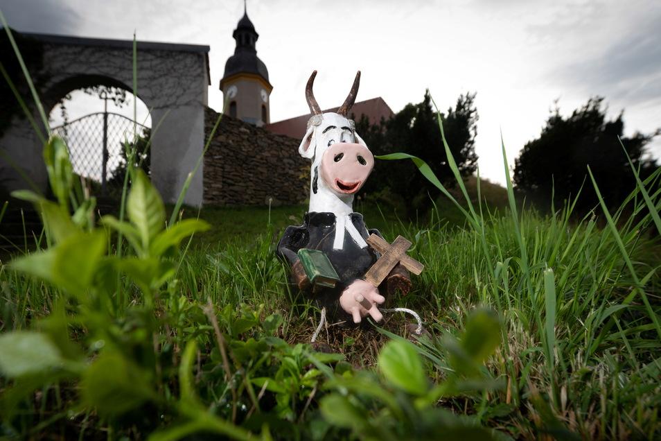 Vor der Kirche ist die Kuh natürlich wie ein Pfarrer angezogen. Das Kreuz darf nicht fehlen.