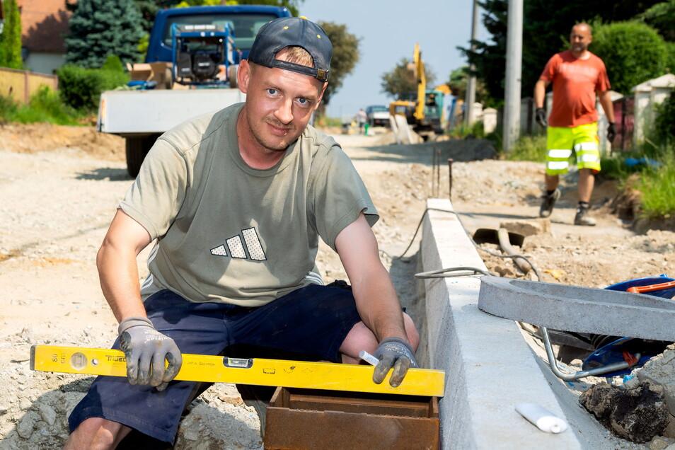 In Kleinbautzen lässt der Landkreis die Ortsdurchfahrt erneuern. Für eine glatte neue Fahrbahn sorgt auch Tiefbaufacharbeiter Felix Socke von der Firma Steinle-Bau.