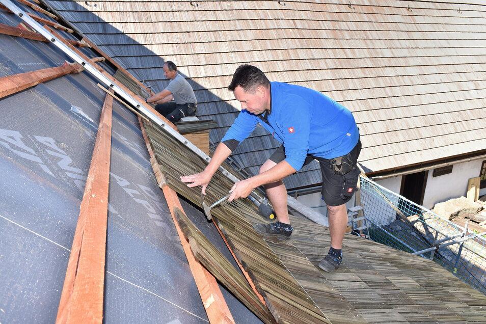Dachdecker Jens Neubert und Andreas Richter (hinten). Bei der Verlegung der Holzschindeln für das Bergbaumuseum ist Geduld gefragt.