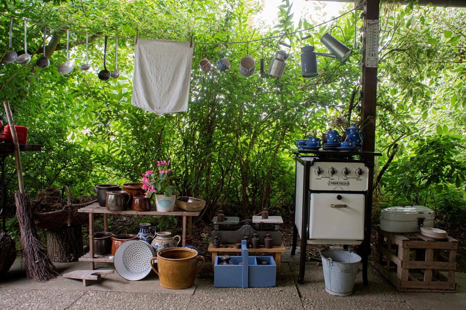 Fast wie auf einem Trödelmarkt: Ausrangierte Dinge des täglichen Lebens, auch ein alter Ofen, stehen an der Terrasse.