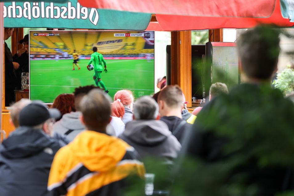 In einem Biergarten unweit des Stadions schauen sich Fans das Geisterspiel an.