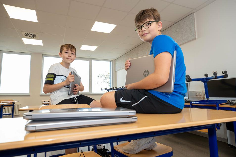 In der Bannewitzer Oberschule Am Marienschacht sitzen die beiden Schüler Leandro (links) und Florian (rechts) mit einem Leih-Laptop in der Hand.