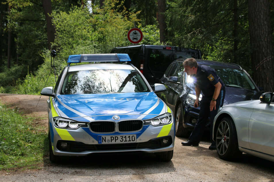 14.07.2019, Bayern, Lauf: Ein Polizist steht auf einem Waldweg an einem Einsatzfahrzeug der Polizei. Ein Pilzsammler hatte zuvor in dem Wald im Landkreis Nürnberger Land einen toten Mann gefunden.
