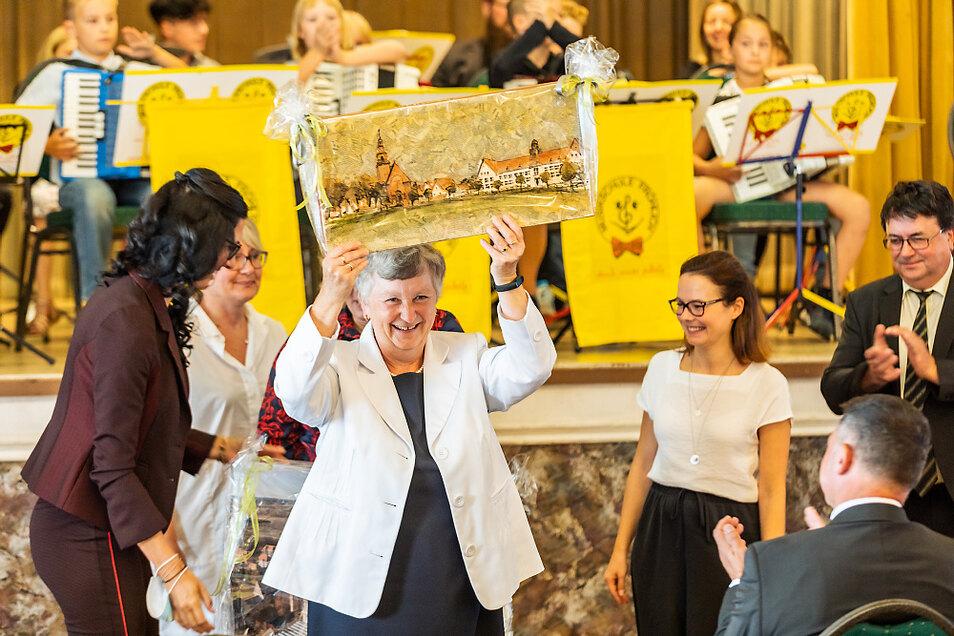 Schulleiterin Monika Simmank mit einem Gemälde, das die Schule am Markt zeigt – ein Elsterheider Geschenk.