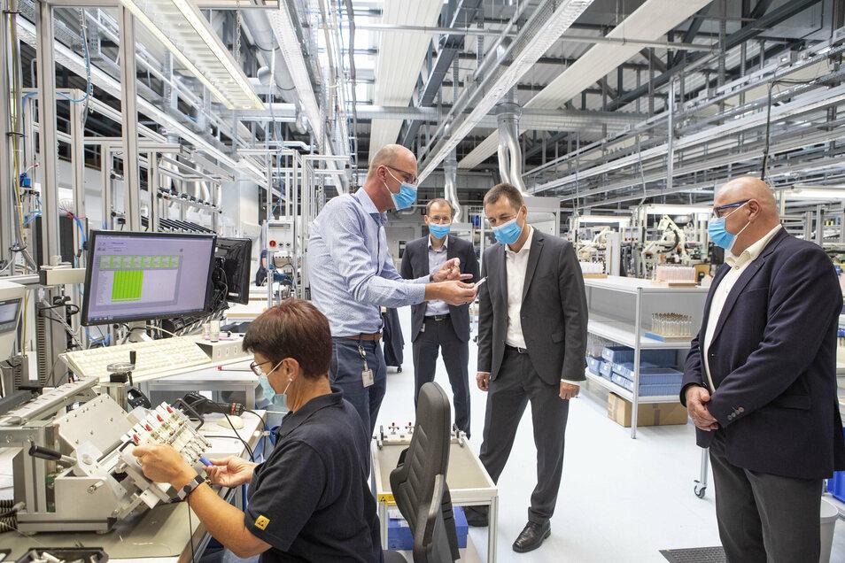 Produktionsleiter Bert Blankenburg (hinten links) erklärt Torsten Herbst (3. von links) die Herstellung eines Sensors zur Flüssigkeitsanalyse. Herbst besuchte auf Einladung von Bürgermeister Steffen Ernst (rechts) das Unternehmen Endress und Hauser.